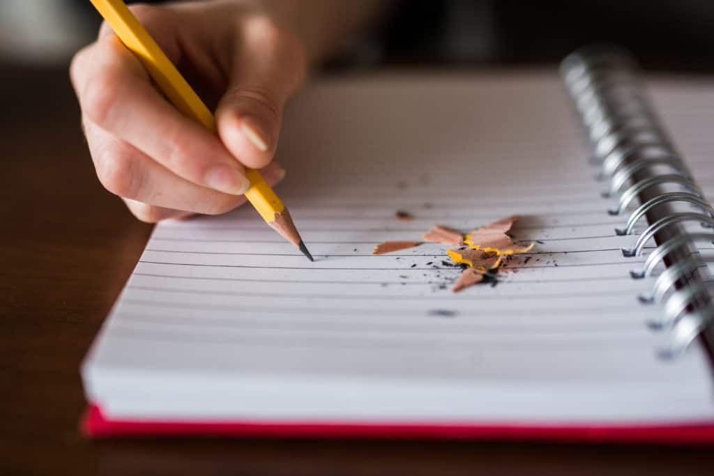 Person writing on a notepad with pencil shavings - Photo by Thought Catalog on Unsplash
